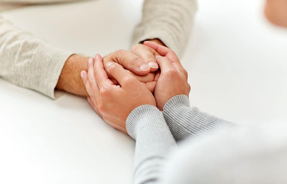 Frau kümmert sich um andere Frau mit Pflegehilfsmitteln